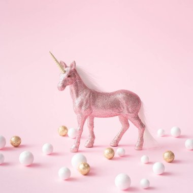 Pink glitter unicorn with gold and white decoration on pastel background, .Magic surreal style, Minimal composition
