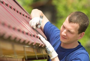 a man in a blue suit repairing the roof of the house, close-up