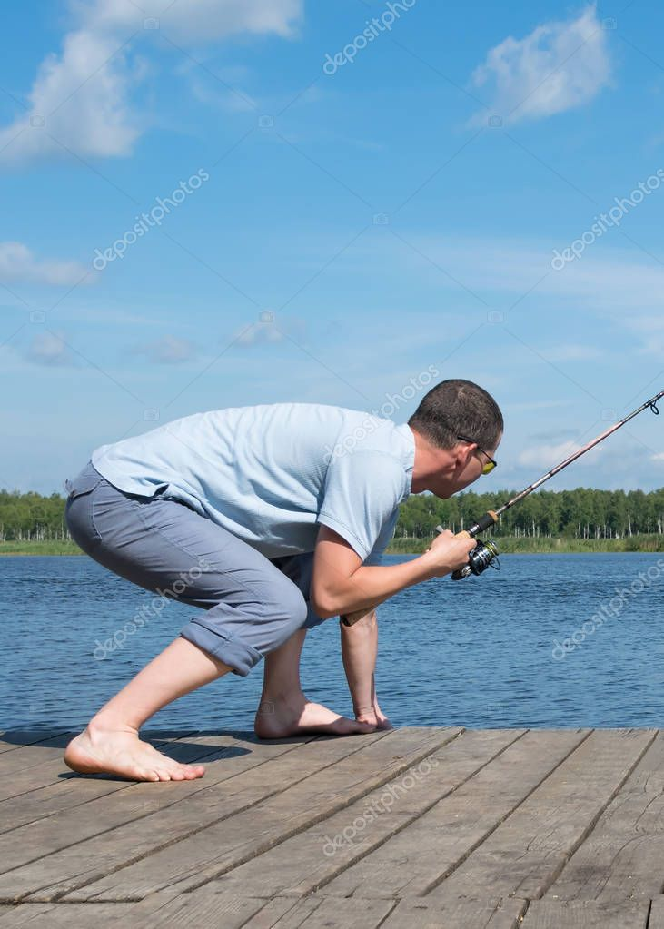 fisherman caught a big fish and wants to pull it out of the water, rear view