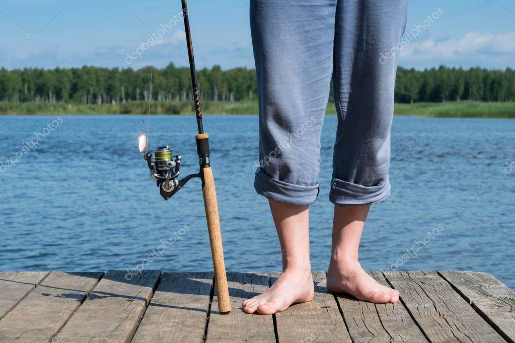 fishing rod and legs of the fisherman stand on the pier, background close-up