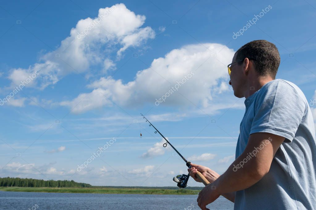 man holds spinning in his hand for fishing against the blue sky