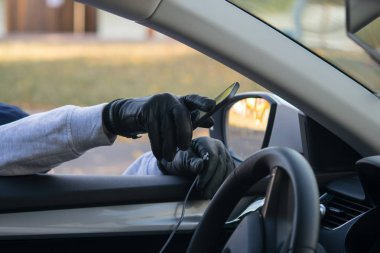 the thief's hand in a black glove, takes the smartphone from the front of the car, through the open glass, breaking the wire