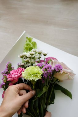 pink bouquet of carnations and roses. woman florist making bouquet of flowers indoor. Female florist preparing bouquet  in flower shop. Close up. Mother's Day and Valentine's Day concept