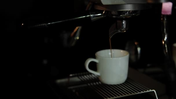 Coffee machine makes espresso in white cup. Soft focus