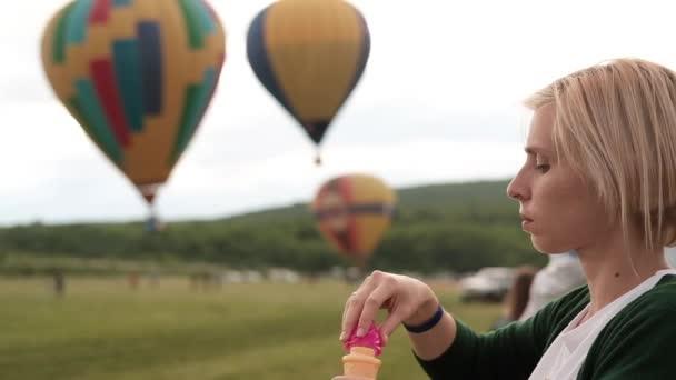 Žena, foukání bublin a tři barevné balon balony na pozadí