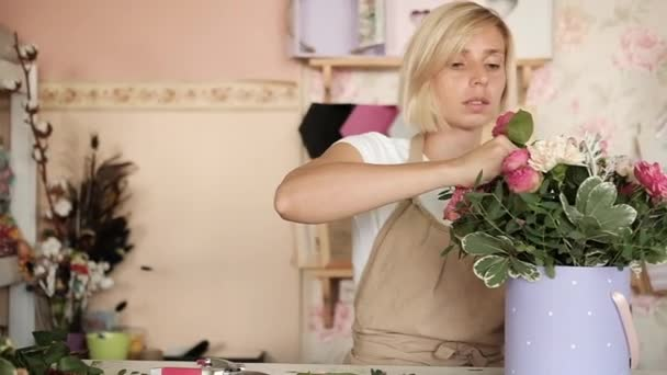 woman florist making bouquet of pink flowers indoor. Female florist preparing bouquet of roses and carnation in flower shop. entrepreneurship, small business, workplace concept.