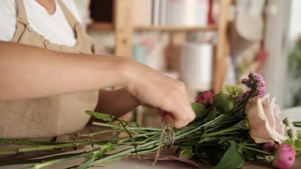 Professional floral artist, florist binding of stems at flower shop, workshop.  Female florist preparing bouquet. Floristry, handmade and small business, entrepreneurship concept. Close up