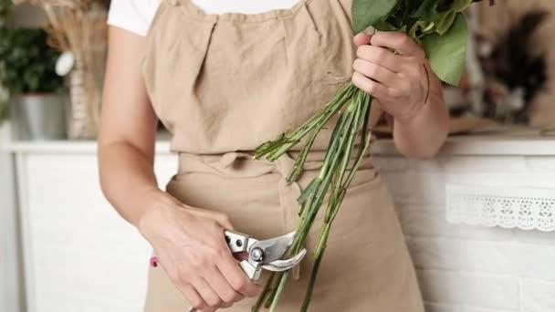 Professional floral artist, florist cutting flower stems at flower shop, workshop.  Female florist preparing bouquet. Floristry, handmade and small business, entrepreneurship concept. Close up