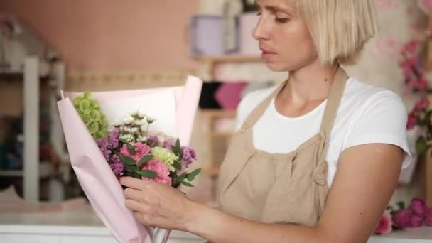 woman florist making bouquet of pink flowers indoor. Female florist preparing bouquet of roses and carnation in flower shop. entrepreneurship, small business, workplace concept