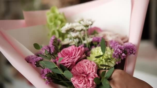 woman florist making bouquet of pink flowers indoor. Female florist preparing bouquet of roses and carnation in flower shop. entrepreneurship, small business, workplace concept. Close up. Slow motion