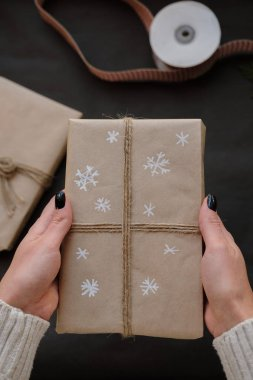 Woman holding Christmas box Gift on black background. Female hands with Presents for winter Holidays. Christmas, New Year, shopping, preparation on Holidays, donation concept
