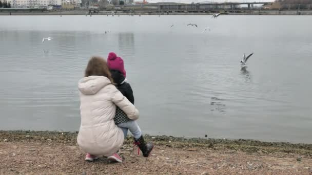 Happy and beautiful mother and daughter are feeding gulls on the beach on the river bank