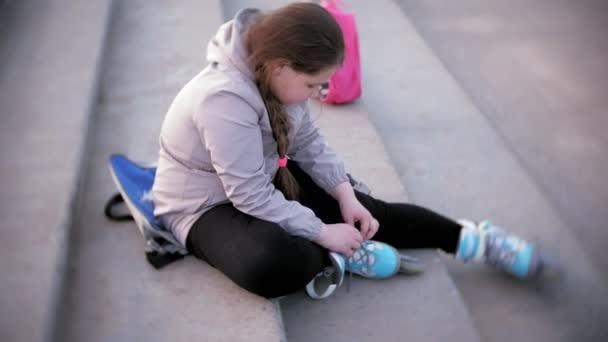 malá holka obléká kolečkové bruslení. Pořadatel: sport, životní styl, zdraví.