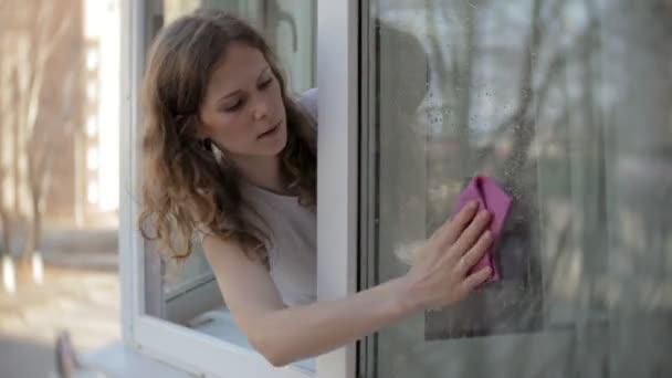 atraktivní holka myje okna doma. Chcete-li vyčistit dům.