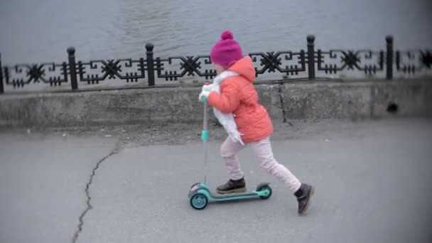 little girl in helmet riding a kick scooter