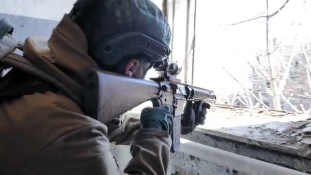 Vojáci v maskování vojenských zbraní, jejichž prostřednictvím puška pohled oknem staré budovy, vojenský koncept