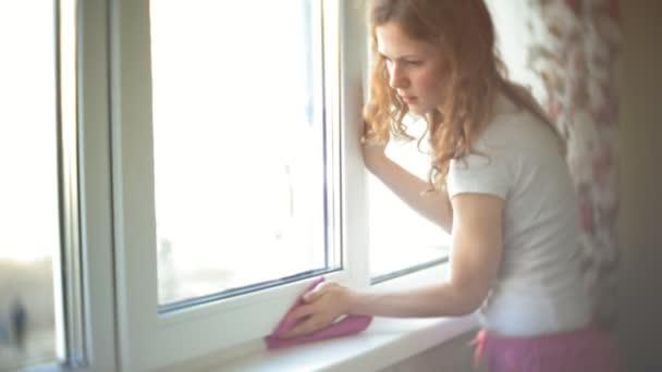 attraktives Mädchen wäscht zu Hause Fenster. um das Haus aufzuräumen.