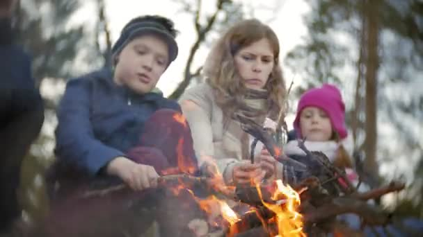 Happy family of tourists on a journey. Mom and children fry marshmallows on the fire near the tent