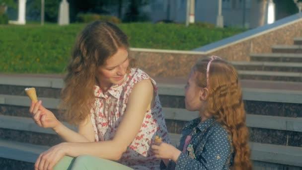 Mutter und Tochter essen Eis in einem Park. Mutter und Kind. Erholsame glückliche Familie