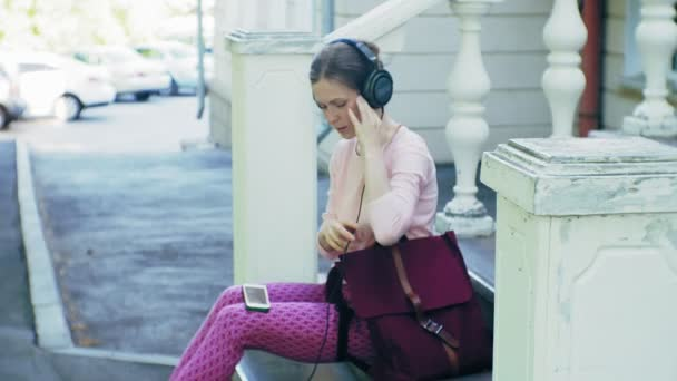 young stylish beautiful woman, on city streets listening to music in large monitor headphones.