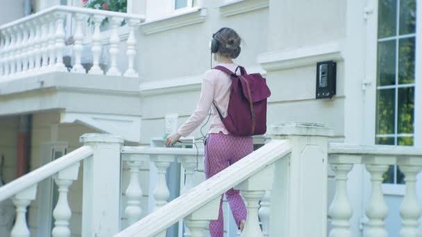mladé stylové krásná žena, na ulicích města poslechu hudby ve velkém monitoru sluchátka