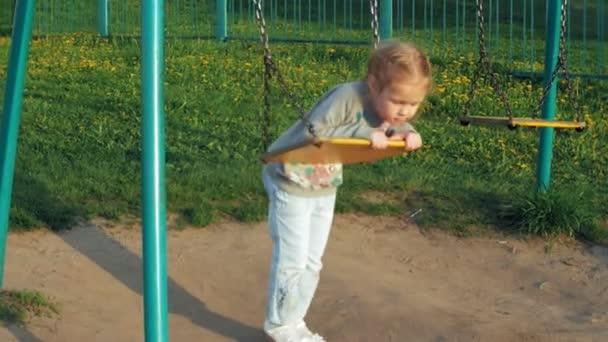 Kind auf einer Folie in Park, kleine Mädchen spielen am Spielplatz, Kinder rutschen