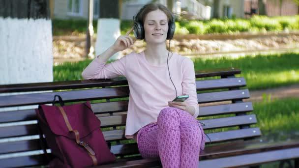 mladé stylové krásná žena, na ulicích města poslechu hudby ve velkém monitoru sluchátka.