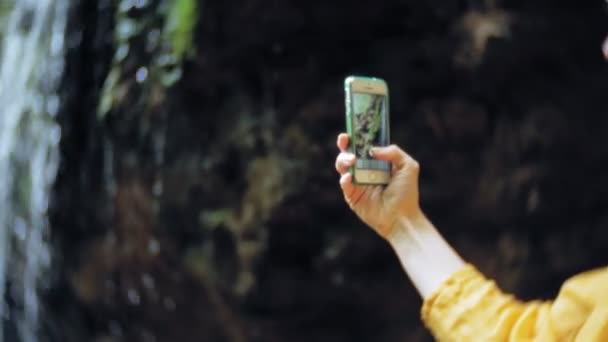 Travel adventure woman taking photos of a smartphone on a mountain waterfall, enjoying the beautiful scenery of nature