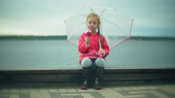 Little beautiful girl with umbrella playing in the rain eating ice cream on the coast
