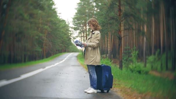 junge schöne Frau trampt auf der Straße stehend mit einem Koffer auf einem Tisch mit der Aufschrift Meer