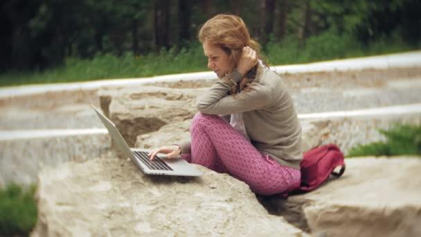 Egy nő, egy laptop ellazítja a sziklák, egy szép zöld parkban. Egy fiatal évelő nő mögött egy laptop dolgozik Arborétum. Technológia a szabadban