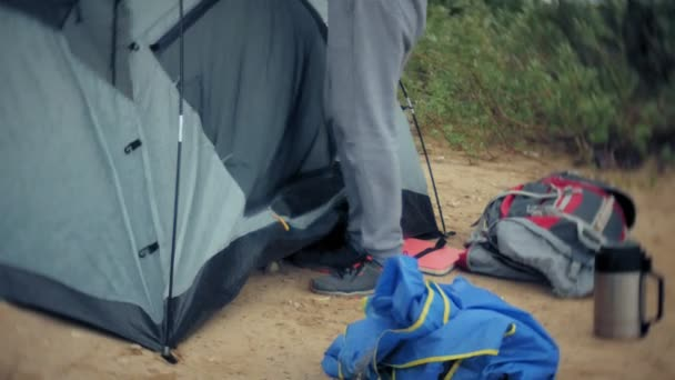 Man collects a tourist tent on the bank of the river of the sea