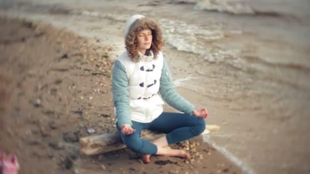 Frau in Lotus-Yoga-Pose im Sand am Wasser