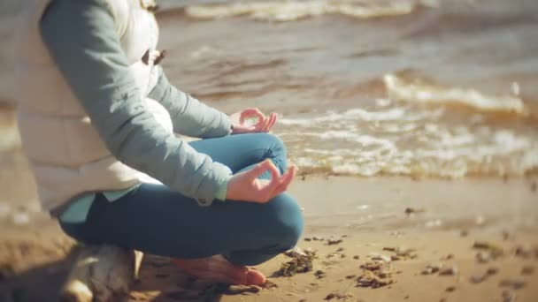 Woman sitting in a lotus yoga pose on the sand near the water