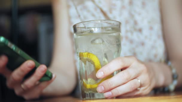 žena pije koktejl v restauraci a používá telefon