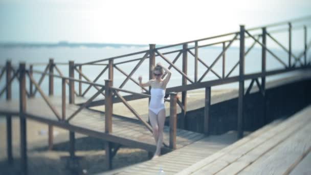 Hot girl standing on the beach on the bridge in the sun. 4k.