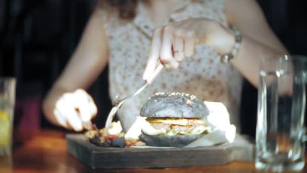 Young woman eating fast food, black hamburger