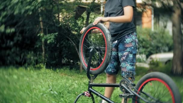 The boy washes his BMX bicycle with water and foam
