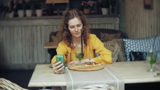 Fiatal nő vesz egy pie egy kávézó, egy okostelefon