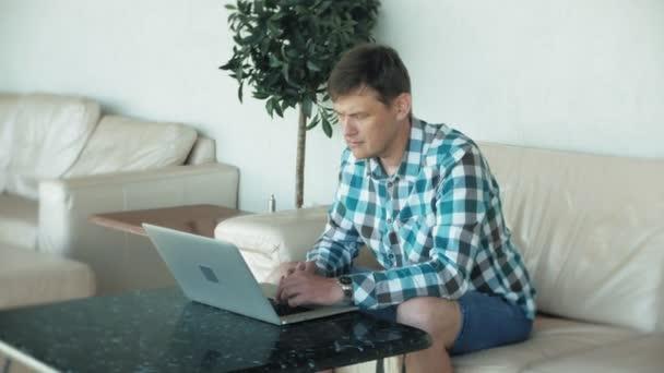 Obchodní muž sedí na pohovce u stolu s tabletu a dívat se skrz papír