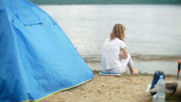 eine Frau isst um einen Wasserkocher auf einem Campingplatz mit einem Zelt im Hintergrund.