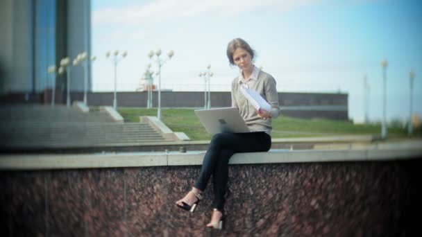 junge Geschäftsfrau sitzt mit Laptop auf der Treppe im Business Center und liest Dokumente.