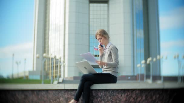 Young business woman sitting on the steps with a laptop in the business center, reading documents.