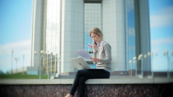 Mladí obchodní žena seděla na schodech s přenosným počítačem v business centru, čtení dokumentů.