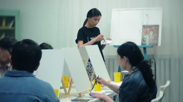 art school, creativity and people concept - group of students with easels, paintbrushes and palettes painting still life at studio, old and young people draw