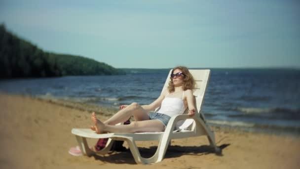 Mladá dívka v bílých bikinách leží a sunbathes na lehátku u moře, písečné pláže