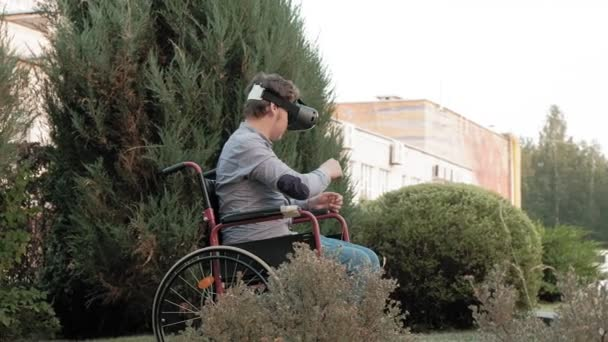 A disabled man in a wheelchair chair uses a virtual reality helmet