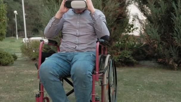 ein behinderter Mann im Rollstuhl entfernt den Virtual-Reality-Helm