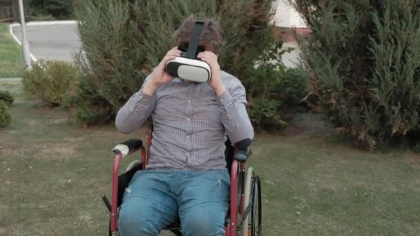 A disabled man in a wheelchair chair removes the virtual reality helmet