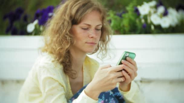 Krásná žena používá smartphone na dřevěné lavičce v parku